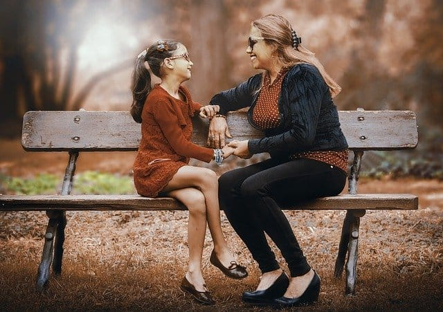 mothe and daughter sitting on a bench wearing eye glasses